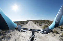 Mountain bike. Forefront of the handlebars of a bicycle on a walk through a barren landscape Stock Image