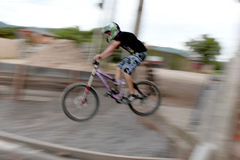 Mountain Bike. R flying down with her downhill bicycle Royalty Free Stock Images