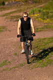 Mountain bike. Young man on a mountain bike up the slope Royalty Free Stock Image