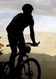 Mountain bike. Silhouette of sportsman and bike at competition in mountain. Sunset Royalty Free Stock Photos