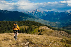 Mountain Bike Adventure. Mature woman mountain bike riding alpine ridge with Treasure Mtn in the distance Royalty Free Stock Photos