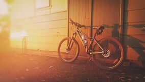 Mountain bike against doorway in sunset evening