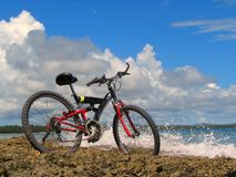 Mountain-bike on beach. Mountain-bike in front of tropical ocean, with vivid colors. With splashing surf and scenic cloudscape in the background Royalty Free Stock Photo