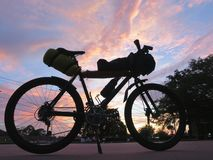 Mountain Bike for bicycle touring and bike packing. Mountain bike loaded with packs and bags for traveling with clouds and sunset in background Royalty Free Stock Photography