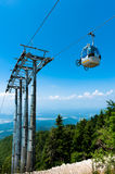 Mountain bike on cable car elevator. Over alpine forest Stock Photo