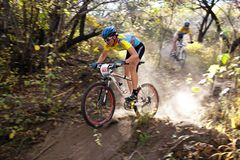 Mountain bike competition in autumn forest Stock Photos