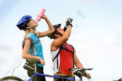 Mountain bike couple drinking. Attractive, healthy couple drink from their water bottles on mountain bikes. active outdoor lifestyle concept Stock Photo