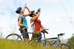 Mountain bike couple drinking. Attractive, healthy couple drink from their water bottles on mountain bikes. active outdoor lifestyle concept Stock Image