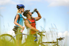 Mountain bike couple drinking. Attractive, healthy couple drink from their water bottles on mountain bikes. active outdoor lifestyle concept Royalty Free Stock Image