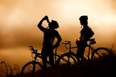 Mountain Bike Couple Drinking In Silhouette Royalty Free Stock Photos