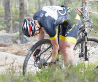 Mountain bike cyclist fixing a flat tire in the forest Stock Photos