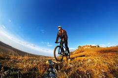 Mountain Bike cyclist riding single track outdoor with blue sky on background. Wide angle. Fisheye. Landscape with hill, blue sky and clouds. Trail. Cyclist Royalty Free Stock Photos