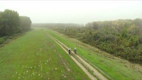 Mountain bike da equitação dos pares em um dia nevoento filme