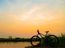 Mountain bike da silhueta no por do sol Fotografia de Stock