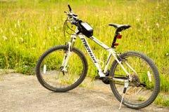 Mountain bike de Merida no campo de grama verde do lado da estrada Fotos de Stock Royalty Free