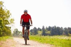 Mountain bike di guida dell'uomo lungo il percorso in campagna Fotografia Stock