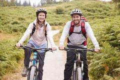 Mountain bike di guida delle coppie adulte giovani in un vicolo del paese, esaminante macchina fotografica, fine su fotografie stock