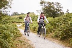 Mountain bike di guida delle giovani coppie adulte nella campagna, integrale fotografia stock libera da diritti