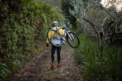 Mountain bike di trasporto del motociclista maschio e camminare sulla pista di sporcizia fotografia stock