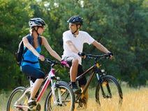 Mountain bike felizes novos da equitação dos pares exteriores foto de stock