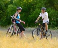 Mountain bike felizes novos da equitação dos pares exteriores imagens de stock royalty free