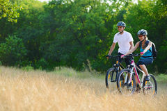 Mountain bike felizes novos da equitação dos pares exteriores imagens de stock