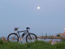 Mountain Bike and Full Moon. Mountain bike parked at shoreline of harbour with dock pier and full moon in background Royalty Free Stock Photography