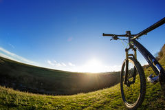 Mountain bike on journeys. Going up hills on small roads between green fields with blue sky. Royalty Free Stock Photos
