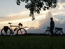 Mountain bike and man with touring bicycle. Mountain bike parked next to man standing with his touring bicycle silhouetted against clouds and sky Stock Photos