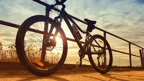 Mountain bike parked against rails. Silhouette of a mountain bike parked against metal rails with a sunset background royalty free stock photos