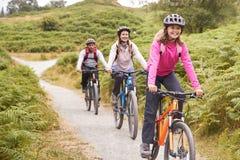 Mountain bike Pre-teen con i suoi genitori durante il viaggio di campeggio della famiglia, fine di guida della ragazza su fotografia stock