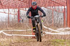 Mountain bike racer with mud. Mountain bike contest on unfinished construction. First edition of Urban Trail Cross Country Short Circuit - XCC inside of Romexpo royalty free stock photography