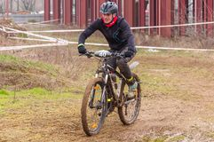 Mountain bike racer on mud. Mountain bike contest on unfinished construction. First edition of Urban Trail Cross Country Short Circuit - XCC inside of Romexpo Royalty Free Stock Images