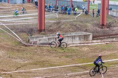 Mountain bike racers on mud. Mountain bike contest on unfinished construction. First edition of Urban Trail Cross Country Short Circuit - XCC inside of Romexpo stock image