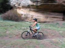 Mountain bike ride. Motion blur of a woman on a mountain bike riding on a trail in front of a rock outcrop Stock Photography