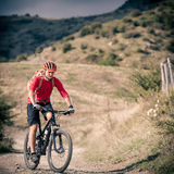 Mountain bike rider on country road, track trail in inspirational landscape. Mountain biker riding on bike singletrack trail in autumn mountains. Man rider stock photography