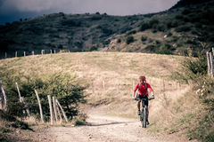 Mountain bike rider on country road, track trail in inspirationa Stock Photos