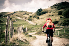 Mountain bike rider on country road, track trail in inspirationa. Mountain biker riding on bike singletrack trail in autumn mountains. Man rider cycling MTB on Royalty Free Stock Photo