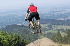 Mountain bike rider jumping precipice. Rear view of mountain bike rider who jumps over a dirt track kicker. The chosen perspective gives the impression of a jump Stock Photography