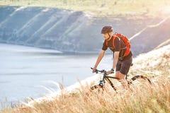 Mountain bike rirding do ciclista atrativo acima do rio bonito no campo no campo Fotografia de Stock