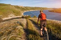 Mountain bike rirding do ciclista atrativo acima do rio bonito no campo no campo Imagem de Stock