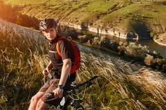 Mountain bike rirding do ciclista atrativo acima do rio bonito no campo no campo Imagem de Stock Royalty Free