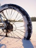 Mountain bike stay in powder snow.  Snow flakes melting on dark off road tyre. Mountain bike stay in powder snow. Lost path  in deep snowdrift. Rear wheel Stock Photo