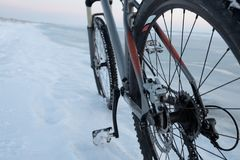 Mountain bike stay in snow near frozen sea or lake. Rear wheel shifter and disk breaks detail. Winter bicycle royalty free stock photos