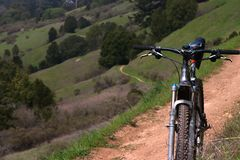 Mountain bike on a trail. Winding hiking trail in the spring Stock Photos