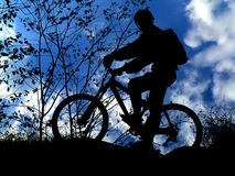 Mountain biker. Silhouette with blue sky stock photography