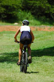 Mountain biker. An active female mountain biker riding her bicycle in nature Royalty Free Stock Photography