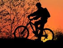 Mountain biker. Silhouette with beautiful orange sunrise stock image