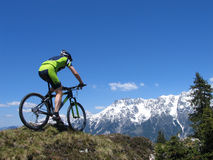 Mountain biker in the Alps. Mountain biker riding through the mountains Royalty Free Stock Images