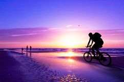 Mountain biker on beach and su Royalty Free Stock Image